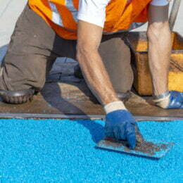 Worker cover playground with rubber coating, mason hand spreading soft rubber crumbs. Outdoor soft coating and floor covering for sports. Rubber mulch for safety and injury prevention. Selective focus.